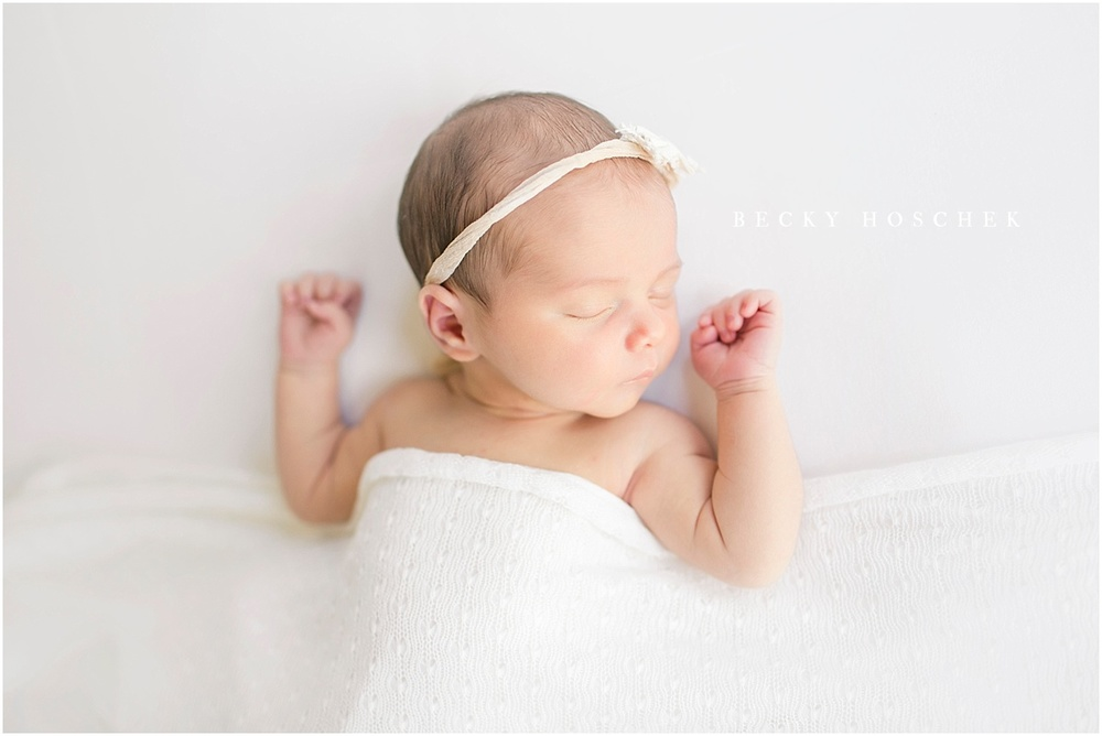 peaceful newborn baby girl sleeping under white knit blanket with tiny fists in the air