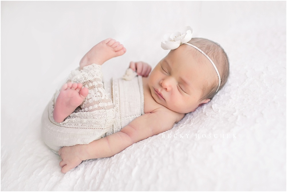 8 day old baby girl in cream lace romper curled up on textured white lace blanket