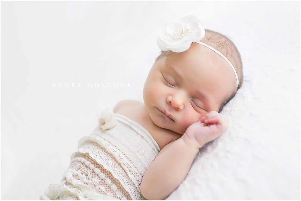 newborn baby girl in natural sleeping pose wearing oatmeal lace knit romper and white floral headband