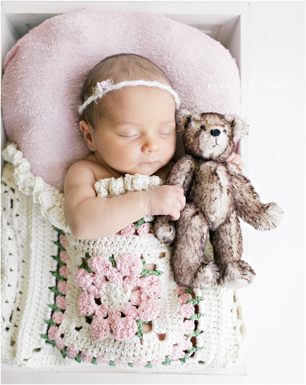 adorable newborn girl lying under pink and cream knit blanket while snuggling with tiny teddy bear