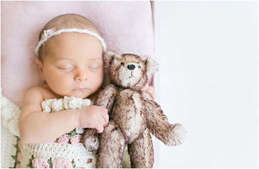 sleeping newborn baby girl with simple white background and brown furry teddy bear