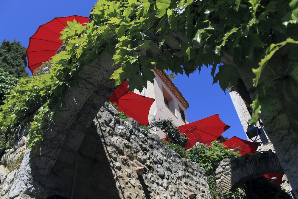 saint paul de vence vines red umbrellas archway stone