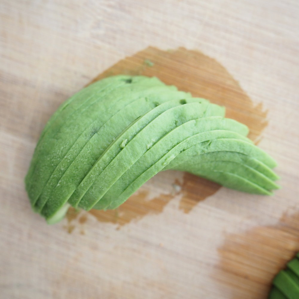 Fan out the avocado so they create a line of slices that overlap each other. Starting from one end, curl avocado slices towards the center.