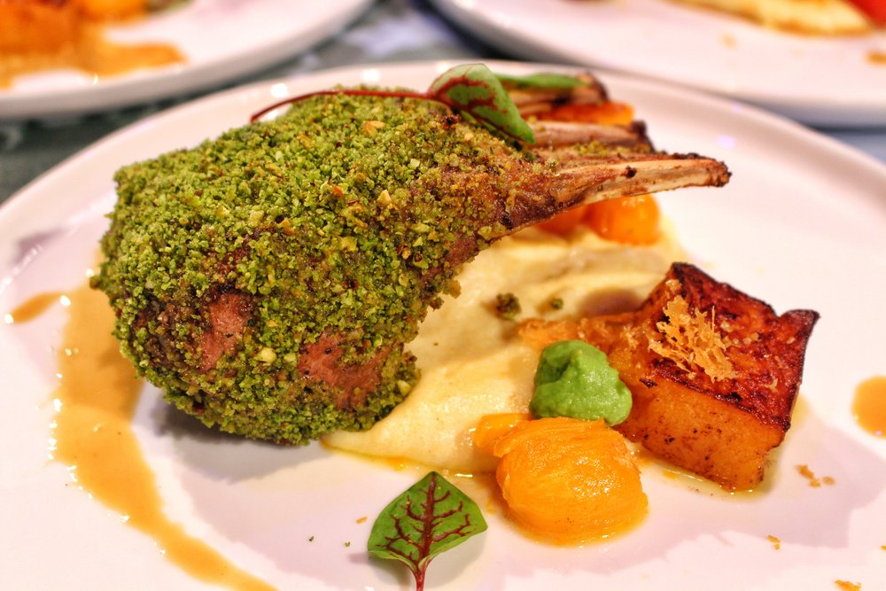Pistachio crusted rack of lamb  -  butternut squash confit, cheesy polenta with roasted bursting garlic tomatoes, bacon jam, parmesan tuile, split pea and tarragon sauce
