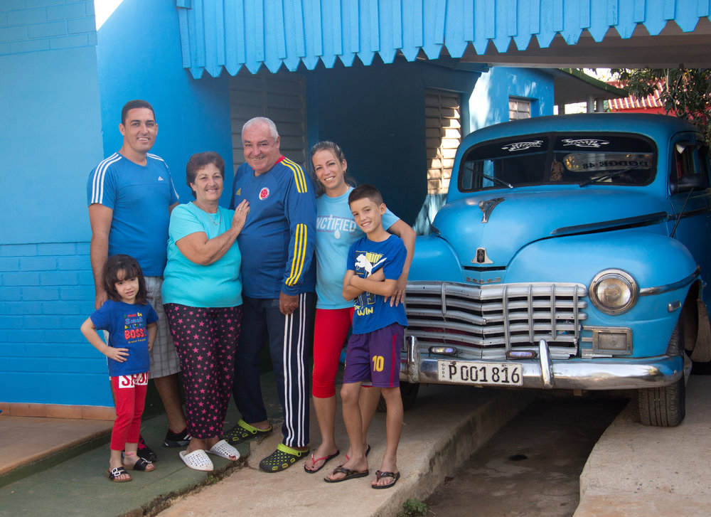 The family in front of the parents home with the great grandfathers' 48 Olds. The blue outfits was my idea.
