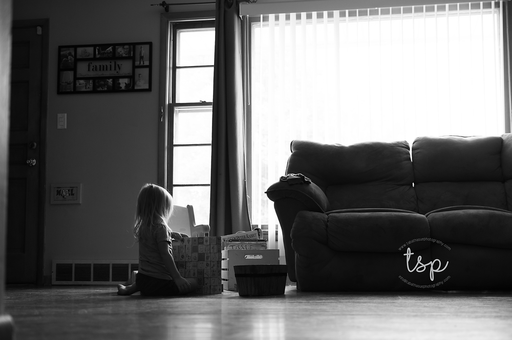 lifestyle-pictures-in-parma-heights-ohio-little-girl-playing-with-blocks-classic-black-and-white-image-documentary-photographer-in-cleveland-ohio.png
