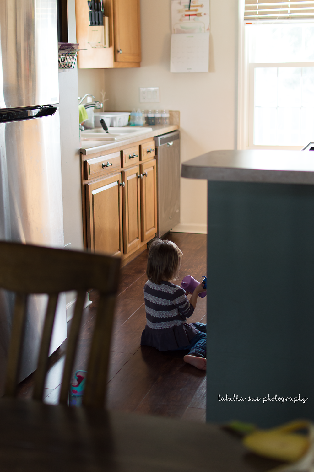 documentary-lifestyle-photographer-near-cleveland-ohio-family-in-cuyahoga-falls-little-girl-sitting-on-kitchen-floor.png