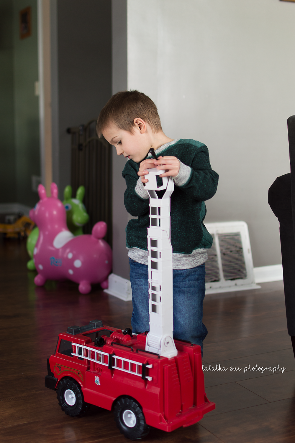 documentary-lifestyle-photographer-near-cleveland-ohio-family-in-cuyahoga-falls-little-boy-playing-with-firetruck-toy.png