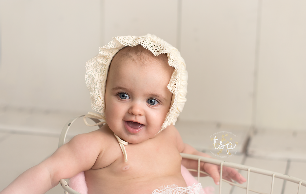 6-month-baby-girl-pictures-near-cleveland-ohio-6-month-session-in-parma-heights-ohio-baby-girl-in-cream-bonnet.png