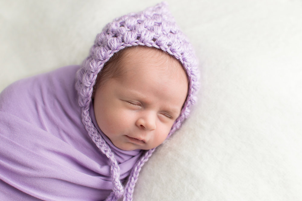 newborn baby wearing a purple bonnet and wrap-simple and clean minimalist-baby pics-photography near middleburg heights ohio.jpg