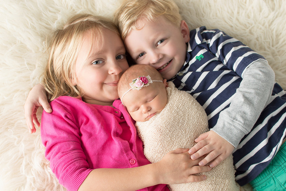newborn picture with toddler siblings-professional photography near me-simple and colorful-cream fur.jpg