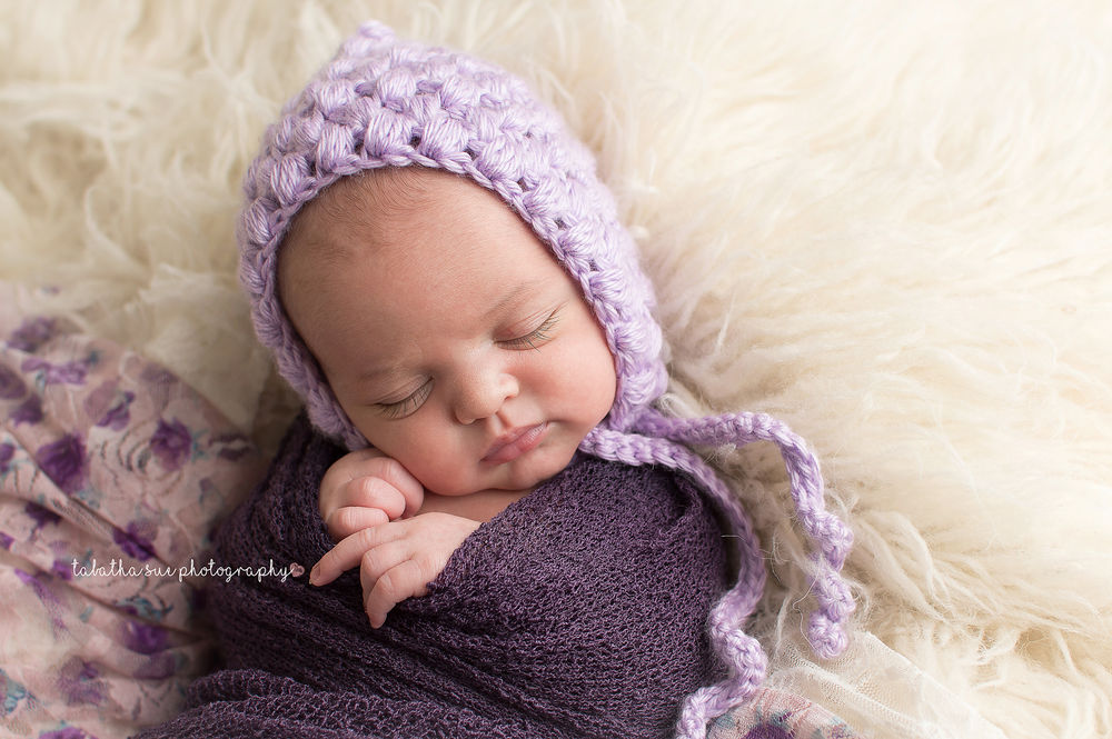 newborn-baby-pictures-wearing-purple-bonnet-and-purple-wrap-on-fur-best-newborn-photographer-in-cleveland-ohio.png