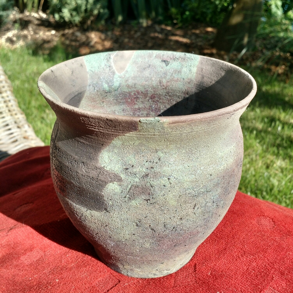 This is my next favourite piece. The black parts are where the white clay body was exposed, without glaze, to the smoke in the box. The carbon has gotten into it and isn't going anywhere. You can see pinkish tinges to the copper green glaze where it has started to 'reduce' to copper.