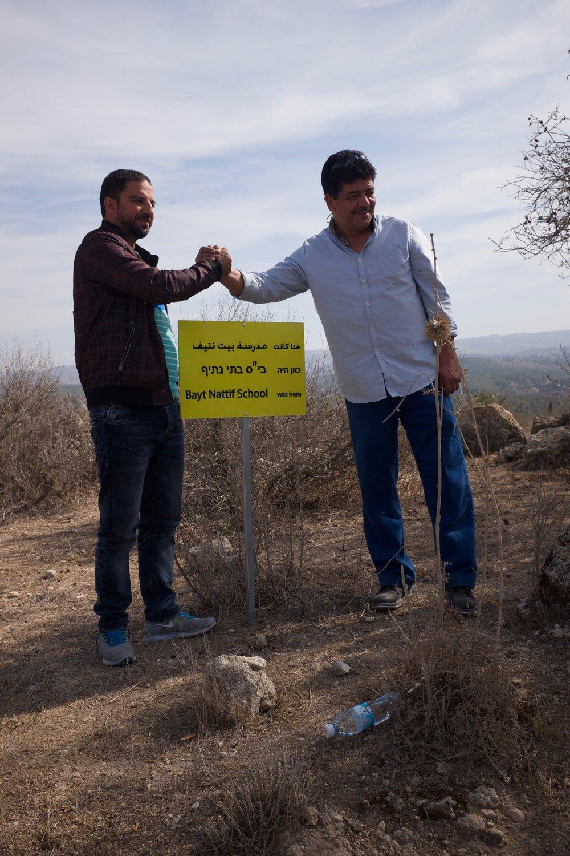 2e en 3e generatie vluchtelingen uit Bayt Nattif plaatsen een bord waar ooit een school stond