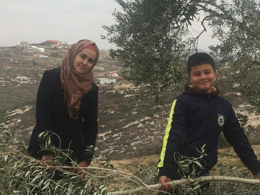 Twee kinderen van Abed Rachman op het land van de familie, met in de achtergrond de outpost Havat Gilad