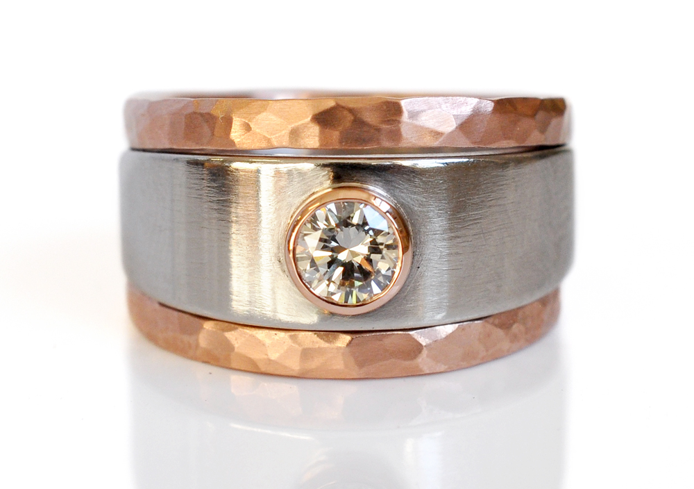 Nordica provided a family diamond for this bold ring stack. Her diamond was remounted into a 14k red gold bezel on an 8mm wide 950 palladium band, with a tapered back and high polish finish. A hammered 14k red gold band stacks on both sides of the engagement ring