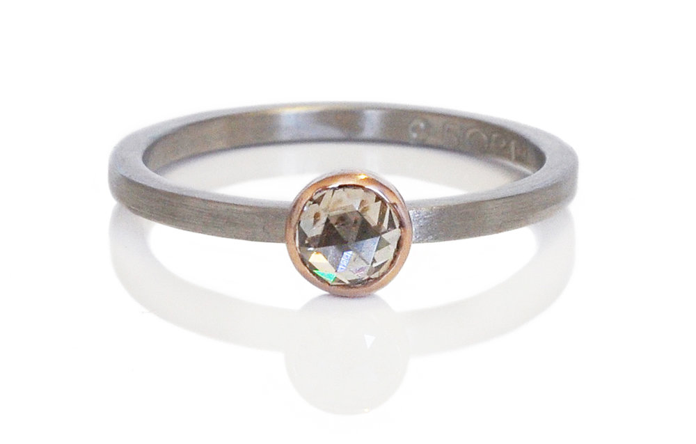 This amazing disco ball diamond throws rainbows all over the place! Set in 14k red gold bezel on a satin finish 950 palladium band. The simple setting lets this diamond do it's thing with no distractions.