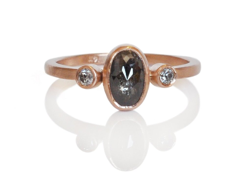 Black and white diamonds add an edge to this soft pink gold setting.