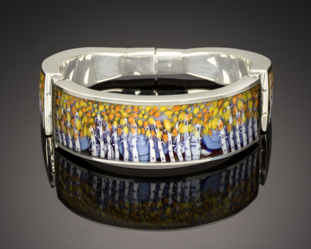 Kevin O'Grady - http://www.kevinogrady.comSculpted by fire on a torch, gold, silver & murrine are suspended in glass.My work strives to show the life & depth possible in glass. Silver is hand forged to present my glass visions in wearable art