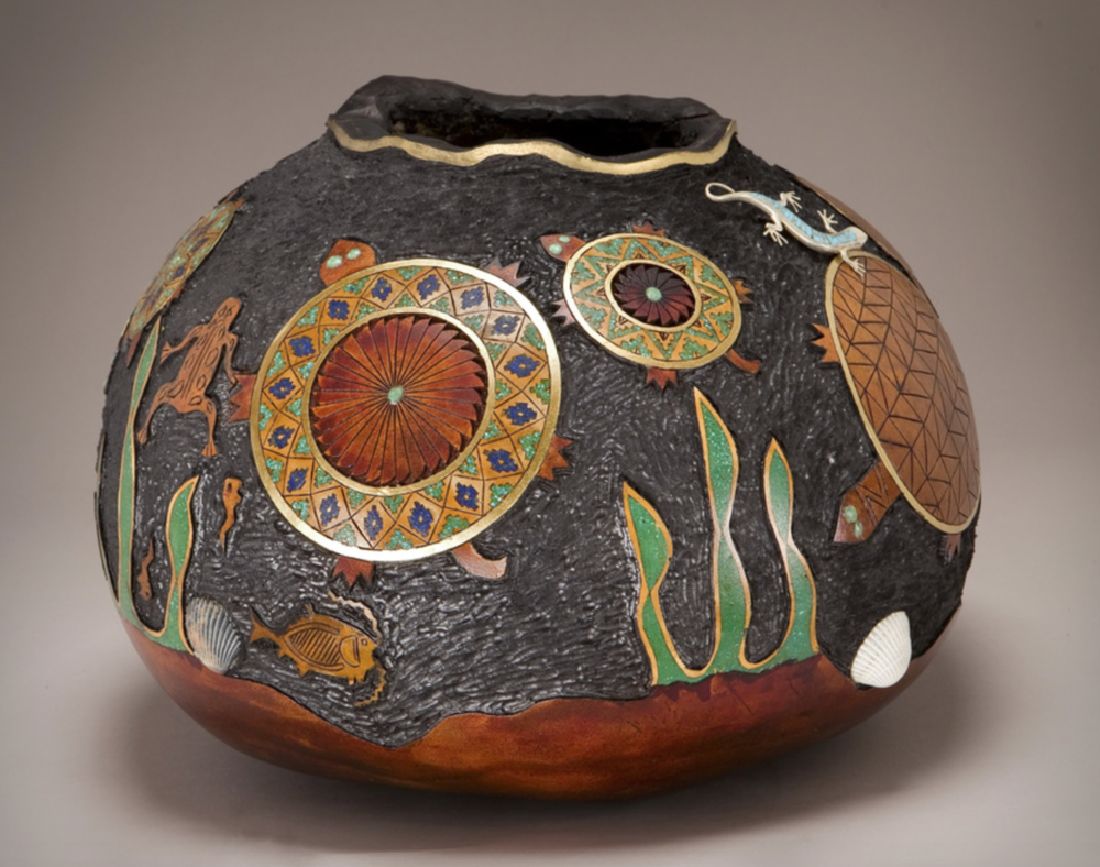 Denny Wainscott - http://Morningdewgourds.comI draw the design on the gourd then I wood burn it. I then carve where I want to inlay my stones. I inlay turquoise, lapis and malachite. I finish carving then I stain it with leather dye.