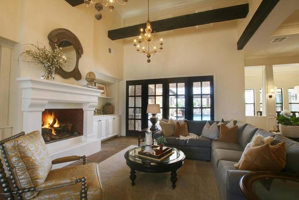 white fireplace mantle with large open fireplace, large wood beams & black door & window casings.