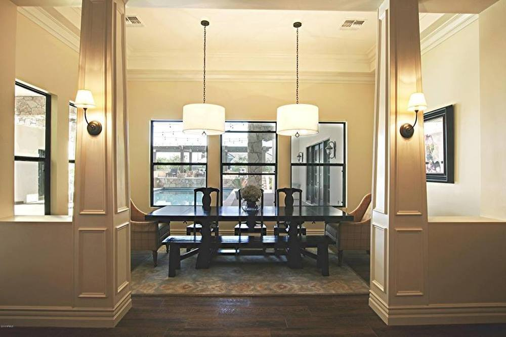 pillars lit by sconce lights leading into the separate dining area with two hanging lights from the trayed ceiling above the table.