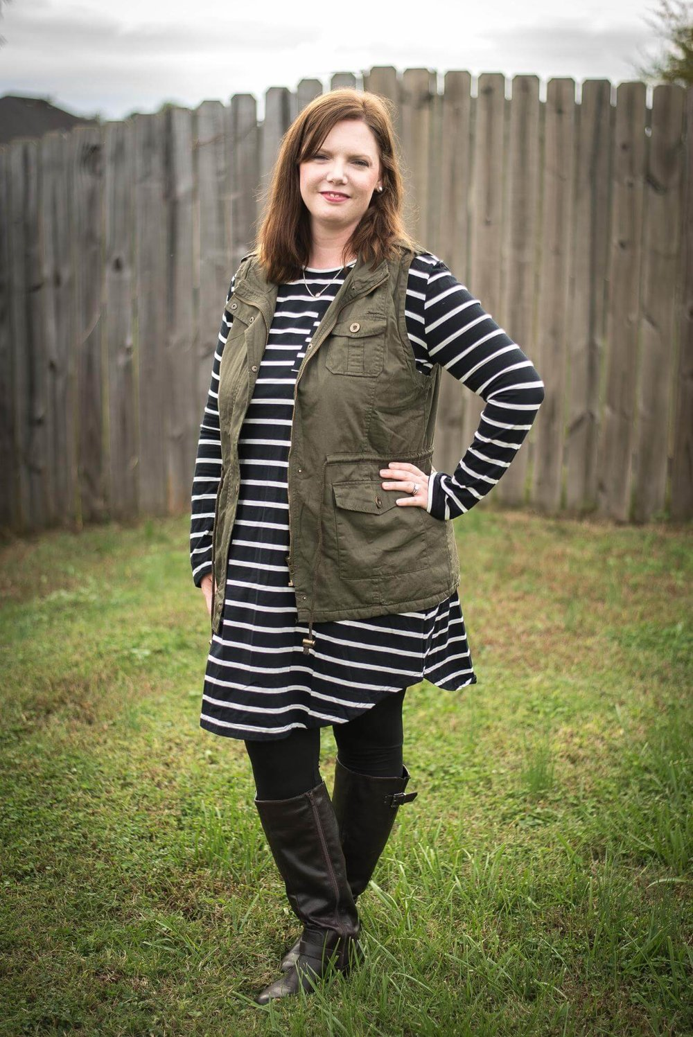 Stripe swing dress + utility vest + leggings + boots... simple but comfy mom outfit! Comfy but stylish mom outfit ideas for fall. These outfits are fashionable but not too trendy! They are all created from a wardrobe capsule-like plan for moms created by the blog. Such a helpful guide for not looking frumpy! And I love the guest blogger's boutique... cute stuff that is actually affordable! Shows you how to style a simple black dress, leopard scarf, denim jacket, striped swing dress, utility vest, plaid scarf, and tunic top! #fall #easy #clothes #mom #fashion #outfits #tips # ideas #easy #style