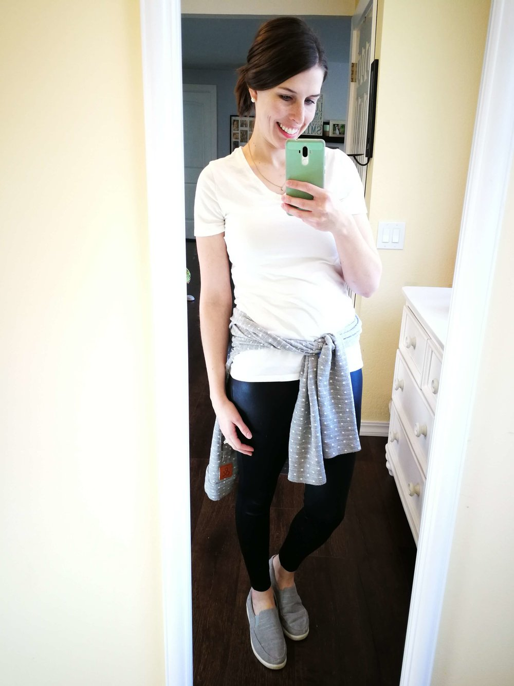 How to wear faux leather leggings in summer or spring. Casual outfit idea for moms that covers your butt- White tee with a sweatshirt tied around waist!