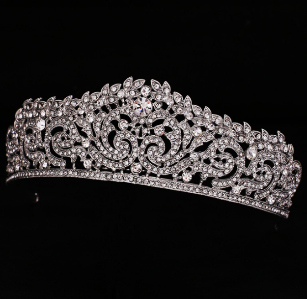 This tiara is a medium profile. Each crystal is set in prongs. It is silver plated and will need to be cleaned, just like silver, it will tarnish. This tiara looks great with either a quinceanera or wedding gown. It is an upgrade for $25