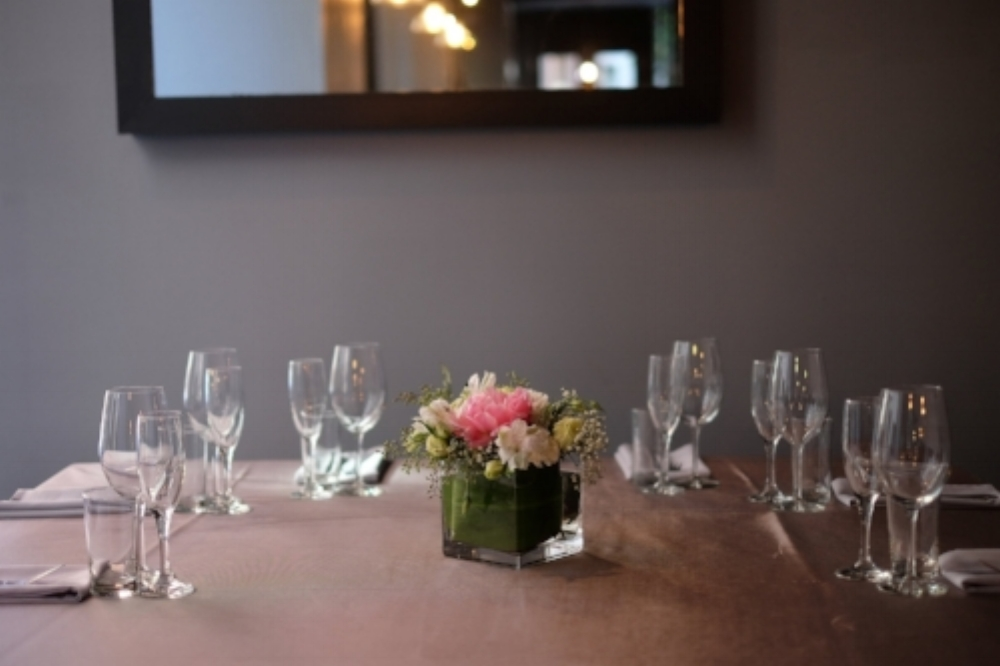 Private event table at Boston Venue display setup with fresh flowers and both wine and champagne glasses.