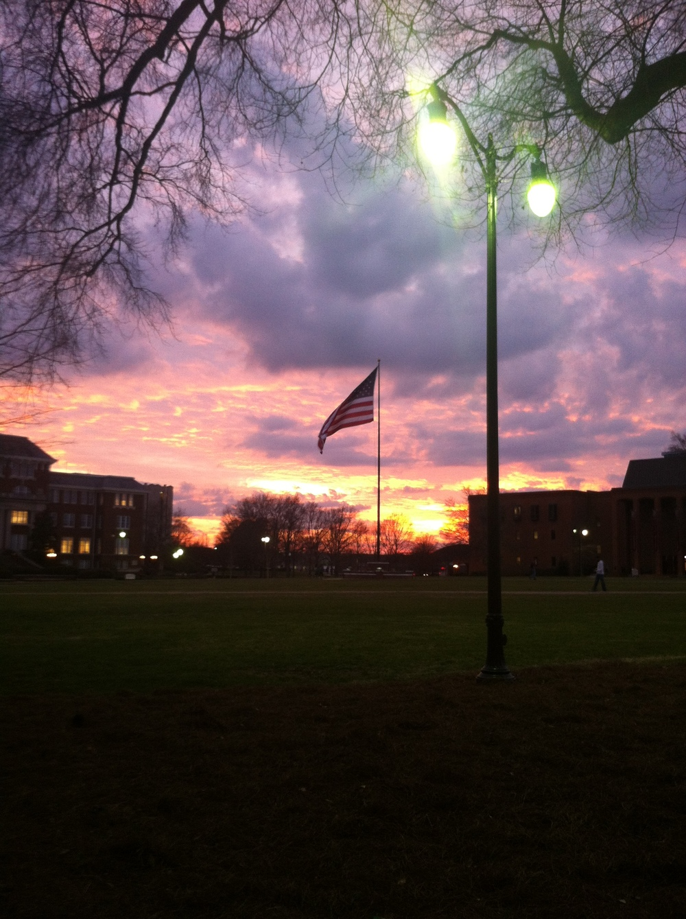 Picture of a sunset and the American flag on Mississippi State University's gorgeous Drill Field