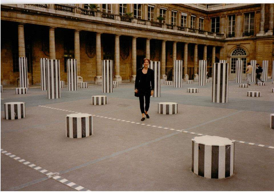 """Susan Manno at the Palais Royal, Paris, amid Daniel Buren's installation, """"Les Deux Plateaux,"""" 1985-86. Photo by Alexander Wood."""