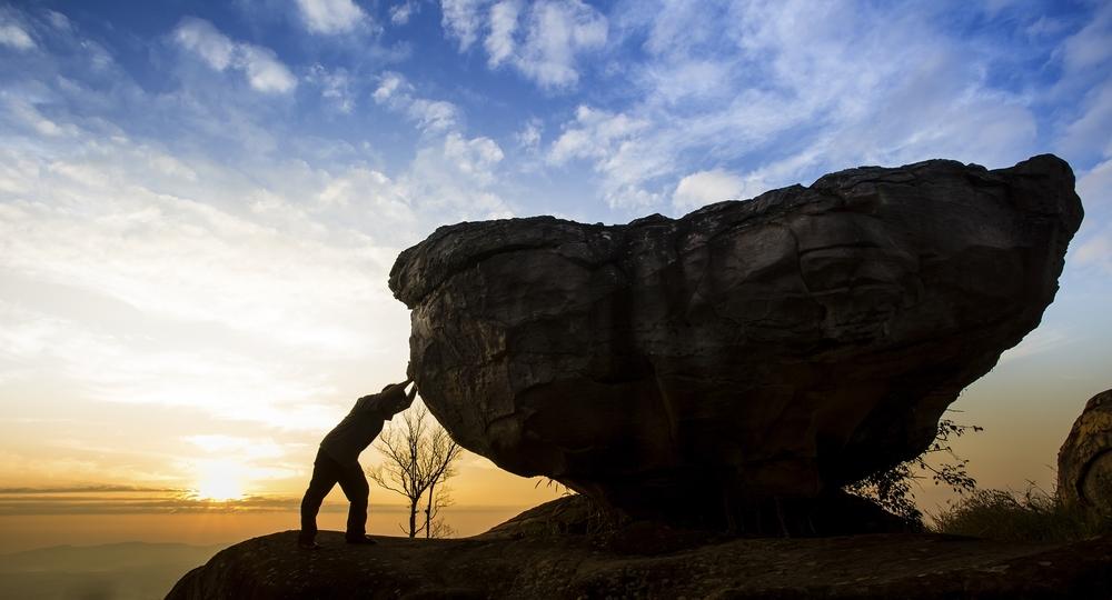 bigstock-Man-pushing-a-boulder-on-a-mou-56958671.jpg