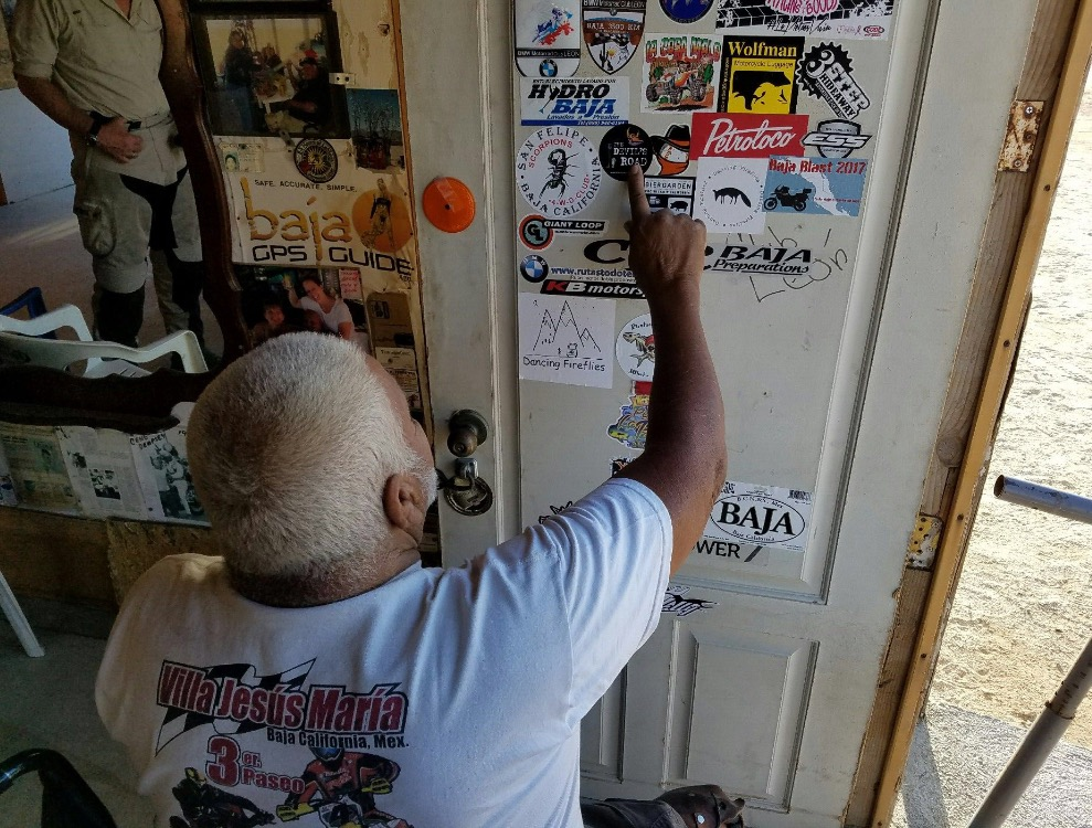 "Coco points to ""The Devil's Roa"" sticker we gave him during our preliminary expedition to Baja. Thank you, Coco!"