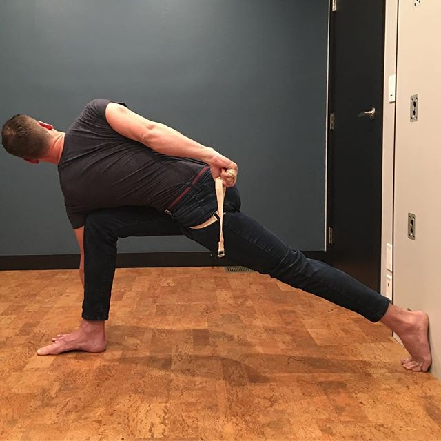 Parivrtta Baddha Parsvakonasana.  Got this from the amazing @practiceyoga.la Wall to punch into with back foot provides balance and direction.  Holding strap  wrapped around greater trochanters to open top shoulder, like a bind, and to lift the straight leg hip up to squared.