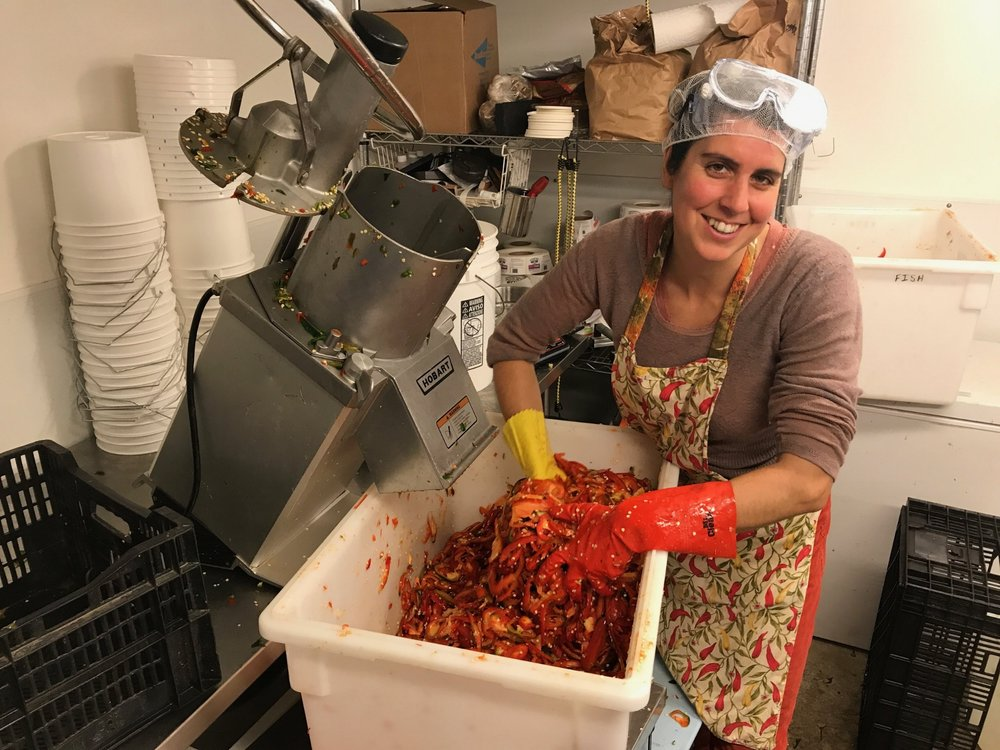 Our co-founder Maddie Elling processing peppers in the kitchen.