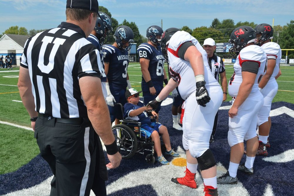 DMD Muscle Champion, Eddie Hazeldine, and the Wesley Football Captains shake hands with Frostburg State to begin the coin toss. Photo courtesy of Wesley College Athletics. Copyright 2016, Wesley College Athletics