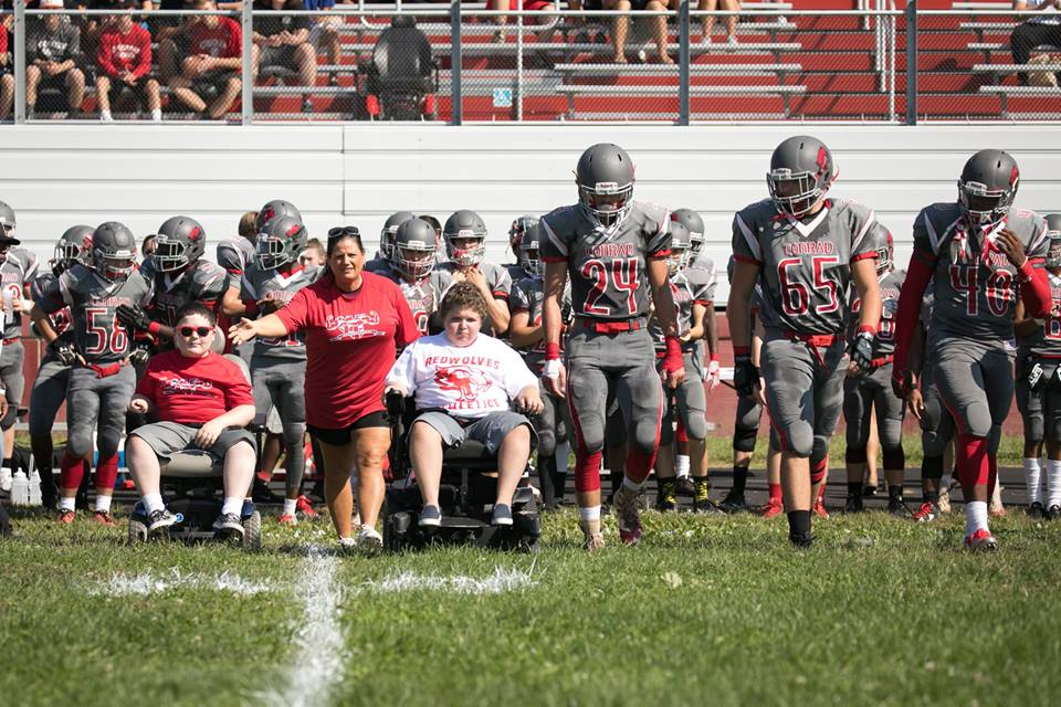 (left) Muscle Champion, Josh Wallace, and (right) Muscle Champion, Eddie Hazeldine, ride to the coin toss with the Conrad Football Captains!
