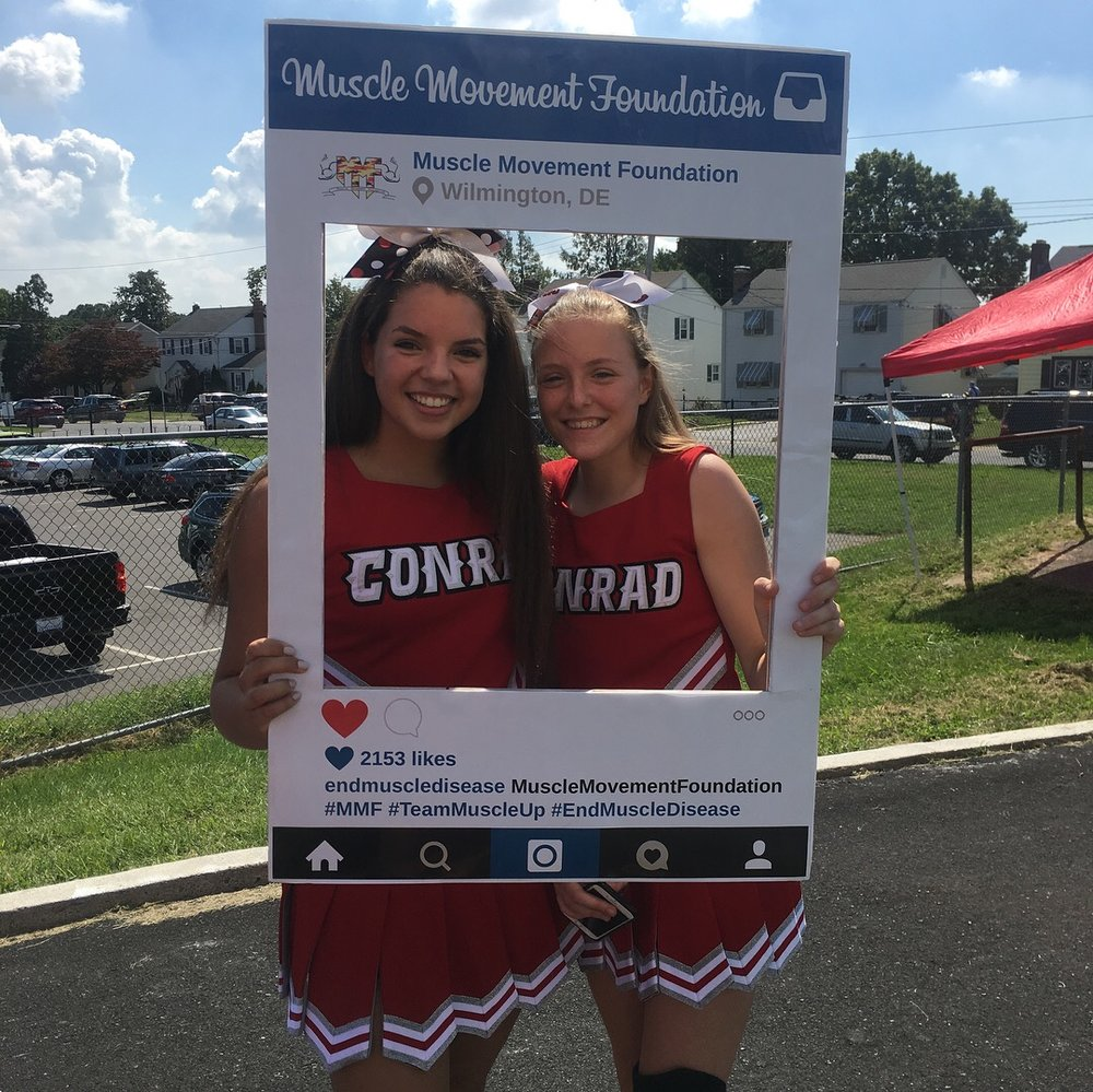Conrad Cheerleaders pose in the Muscle Movement Fnd. Instagram frame!