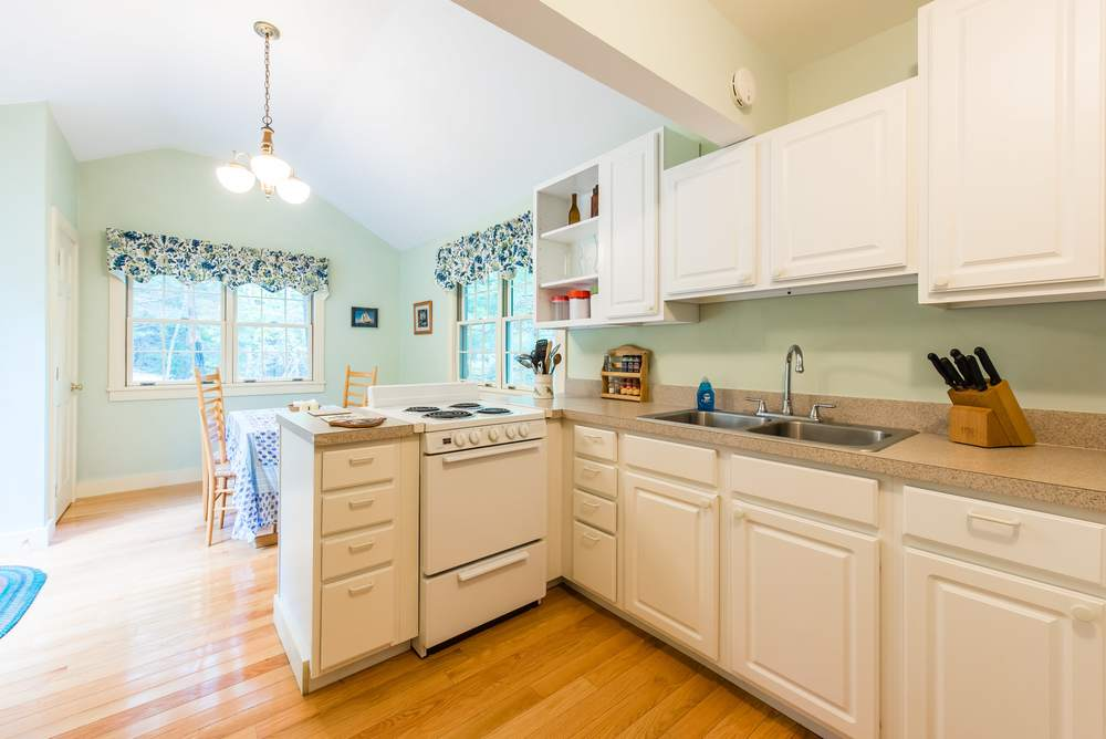 Large, well equipped kitchen with dining area and doors leading to an outdoor patio.