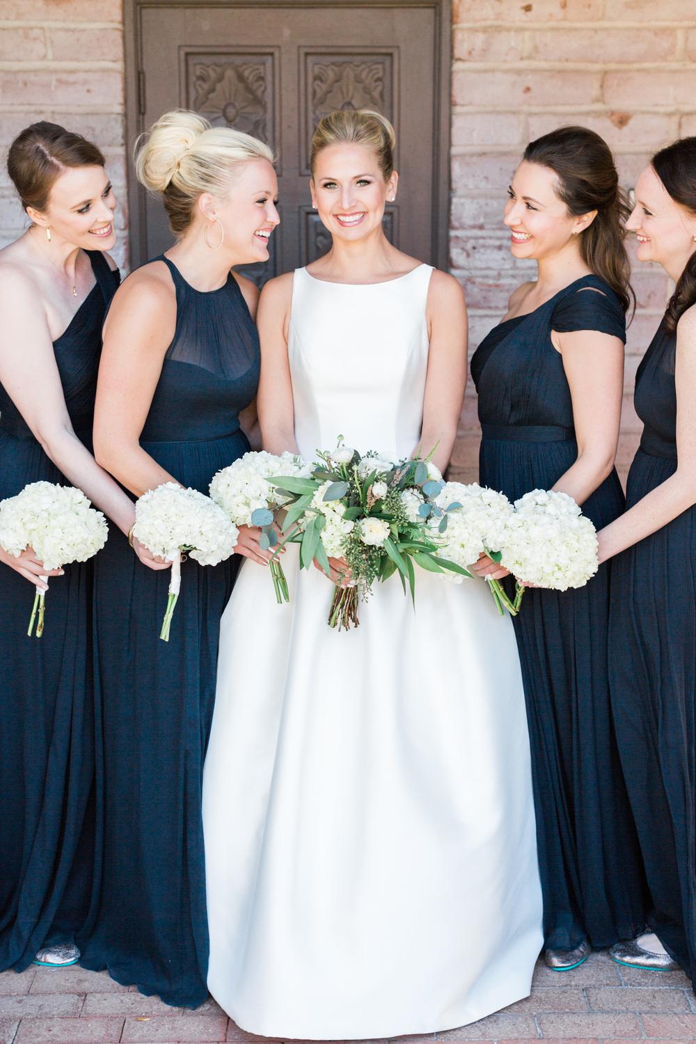 Gorgeous bride smiling at camera with her bridesmaids in navy blue