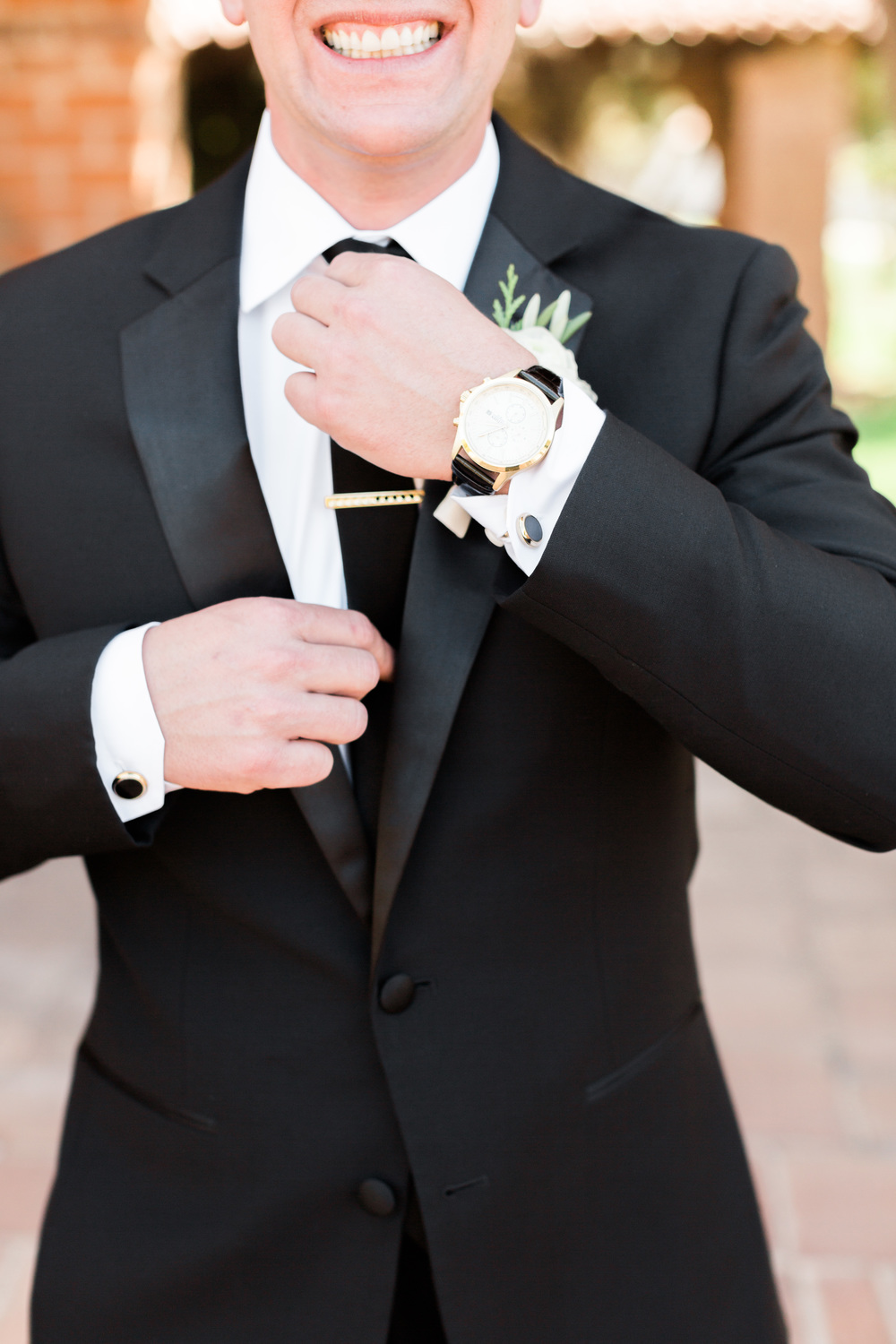 Groom smiling in back tux, straightening tie