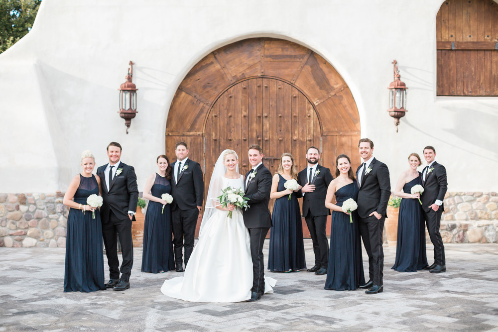 Stunning bridal party wearing floor length navy gowns and black tuxedos