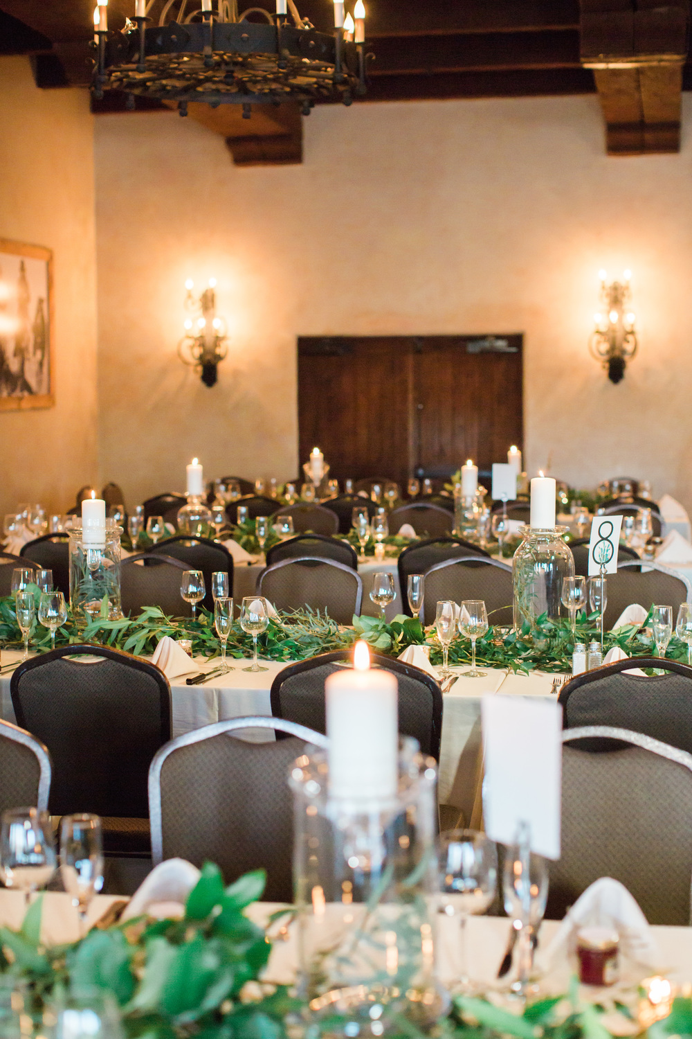 Elegant green and white wedding reception set up covered in candles