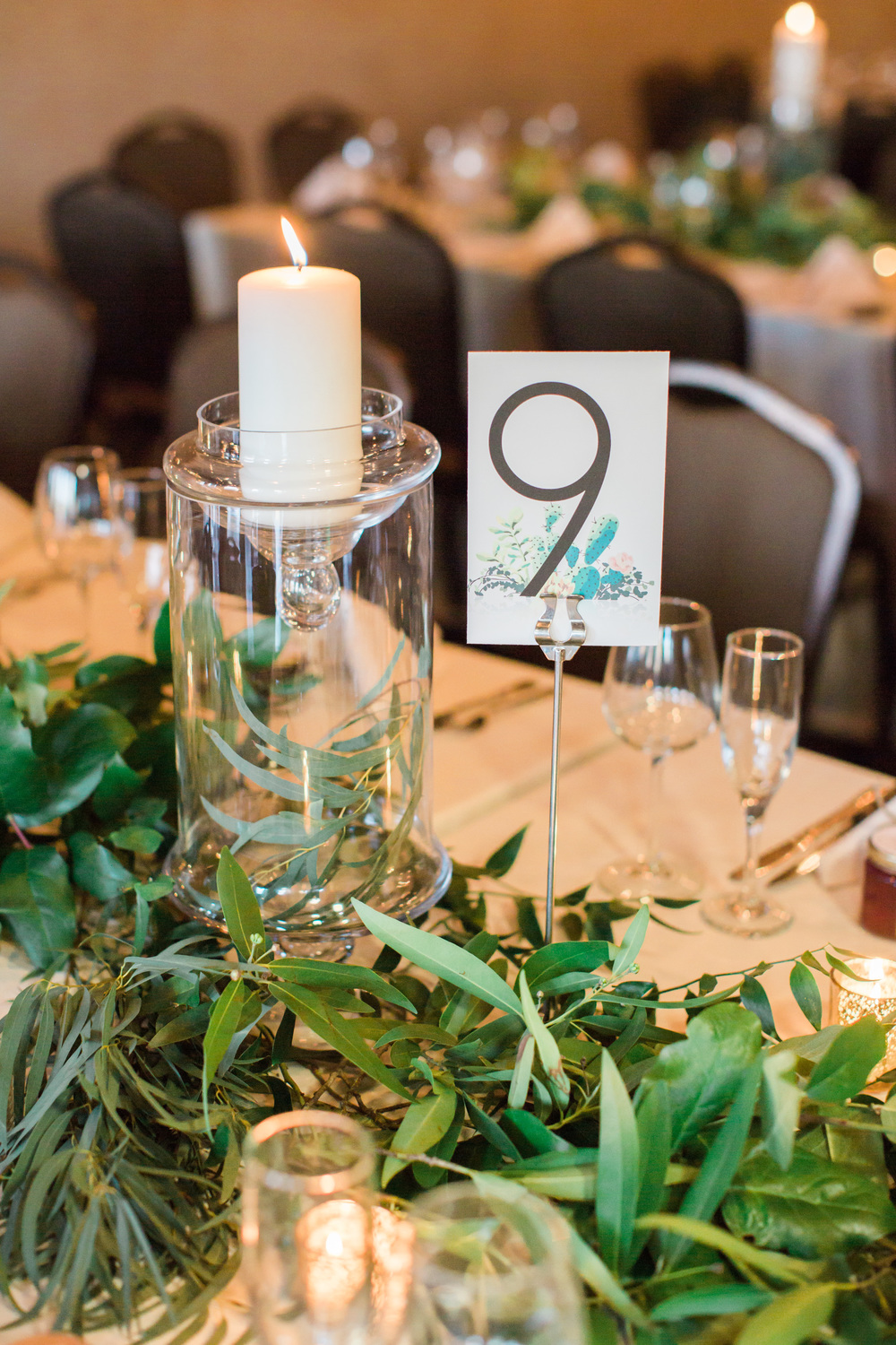 Tables draped in greenery and covered in candles. Table numbers designed by Gorgeous place cards design by briedumaisdesigns.com