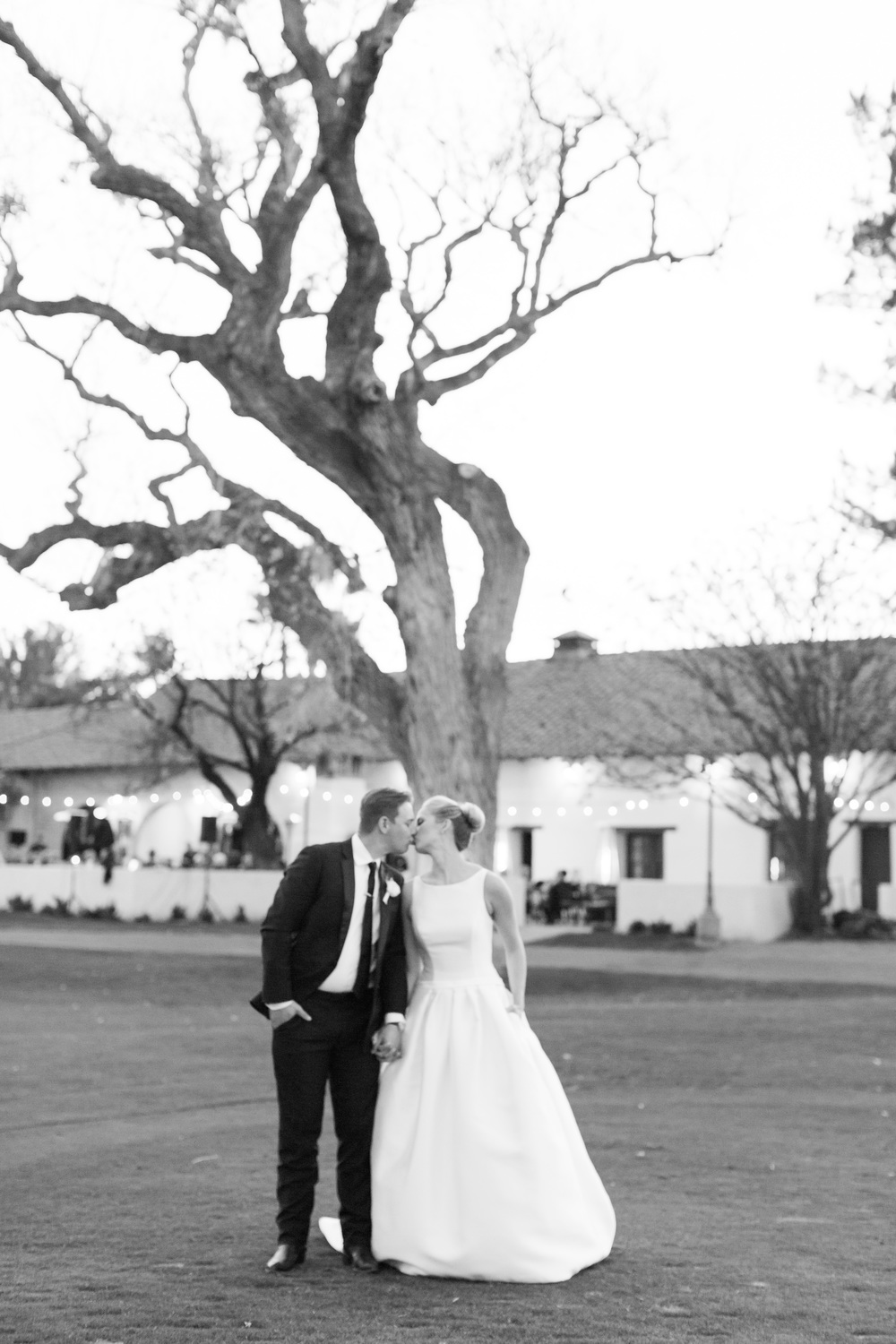 Bride and groom kissing in front of huge tree