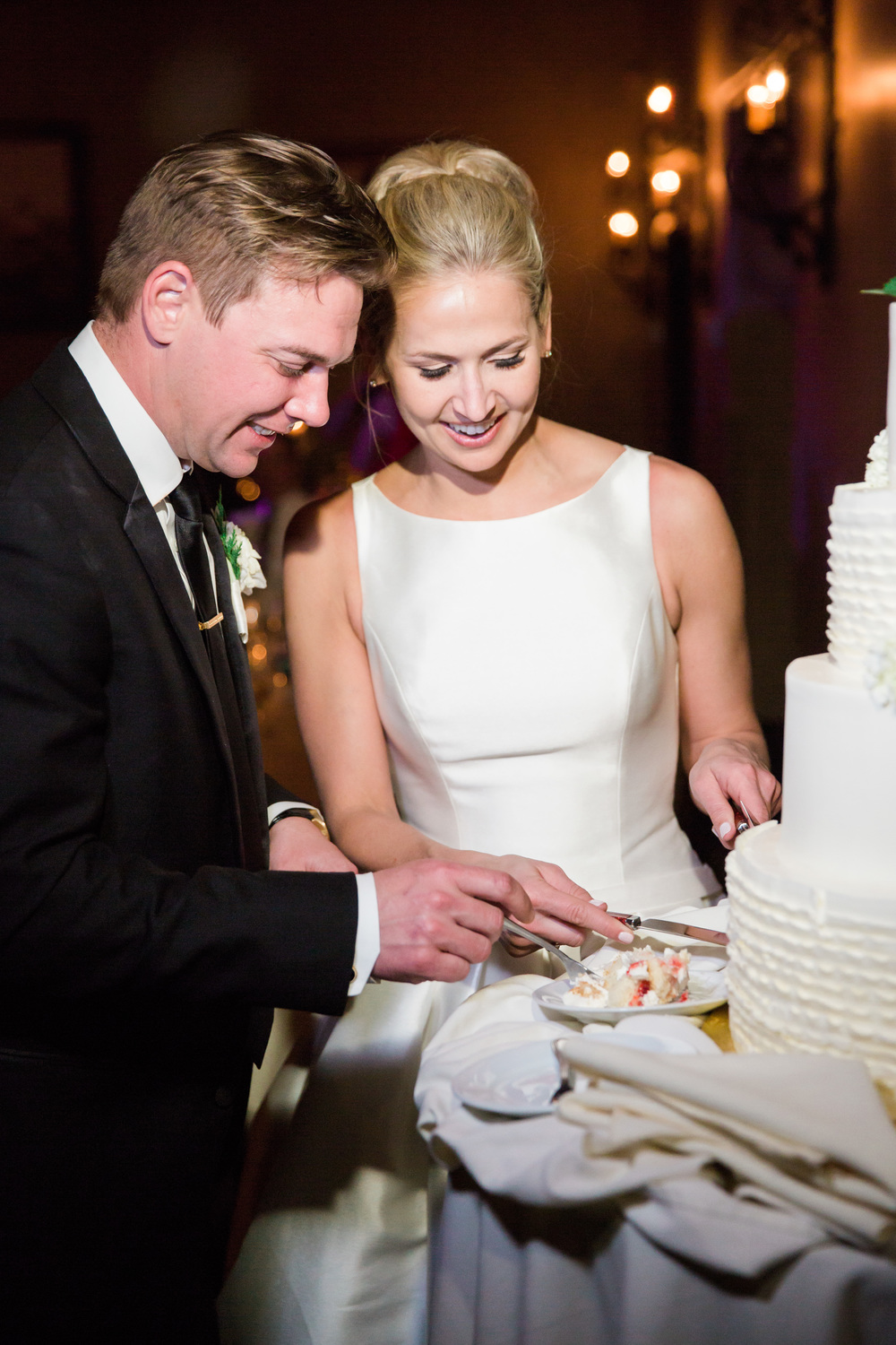 Cutting the gorgeous white wedding cake from Village Bakehouse