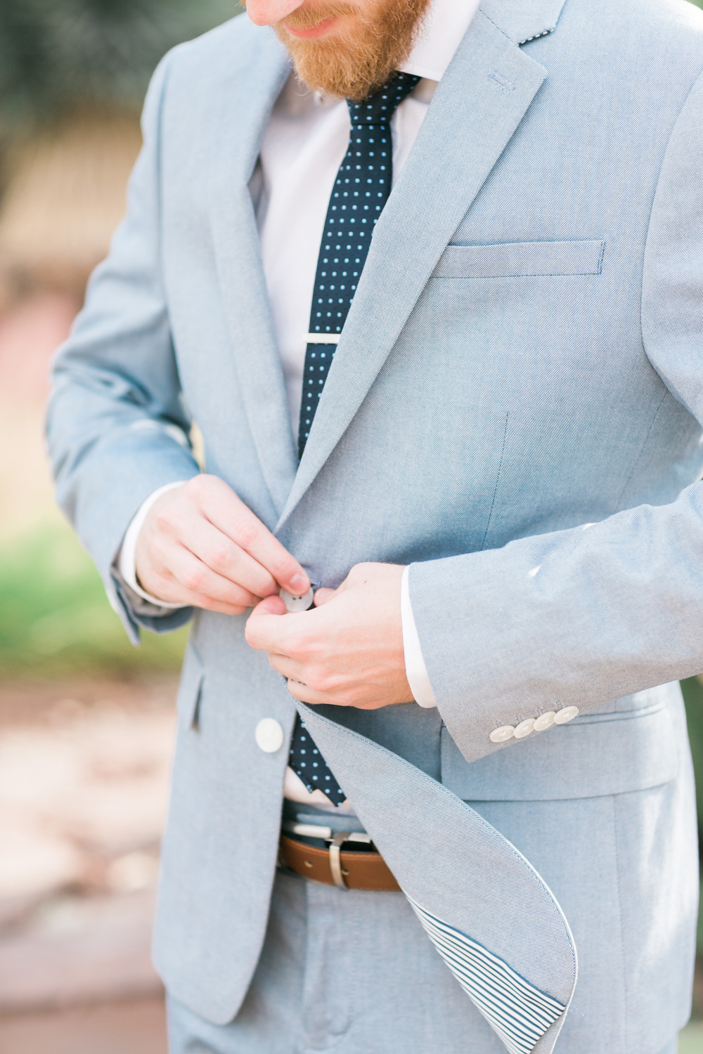 Groom buttoning his light blue suit with seersucker lining from Express