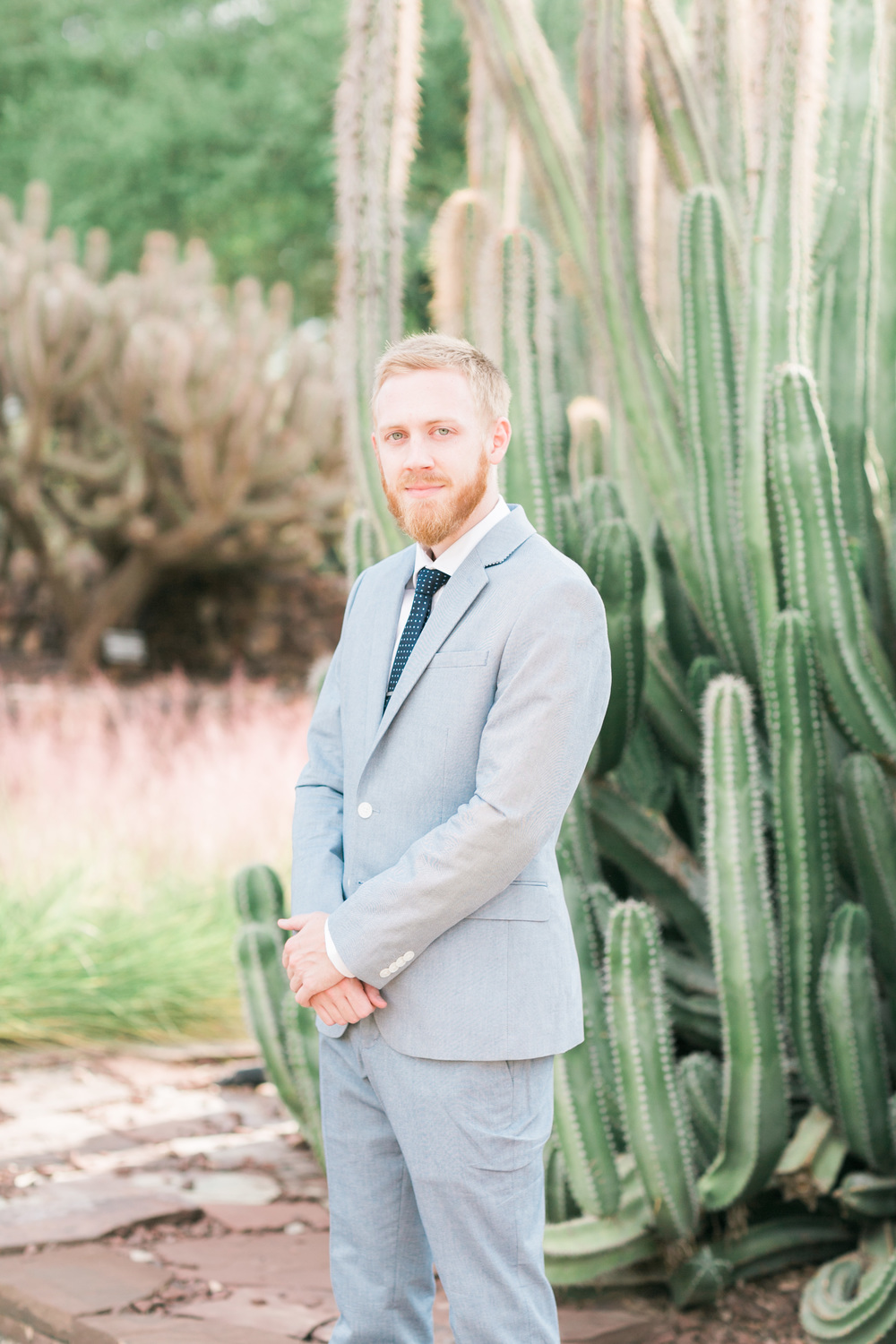 Groom in light blue suit with cactus in the background