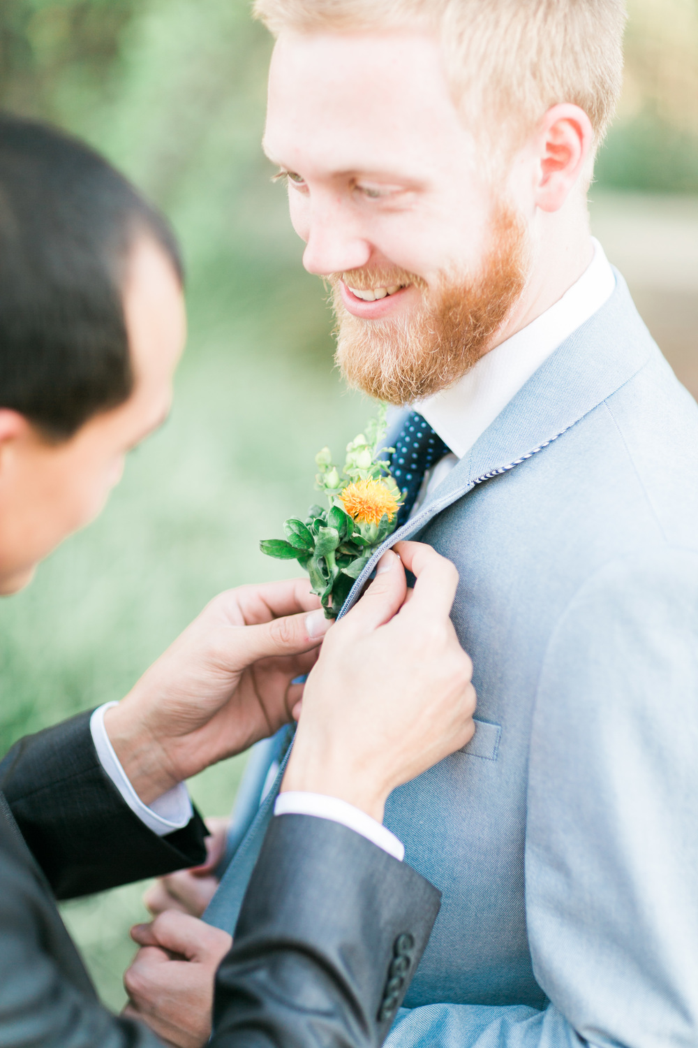 Groomsmen pinning on groom's boutonniere